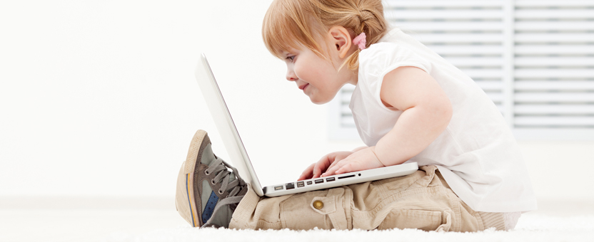 toddler holding a laptop in her lap
