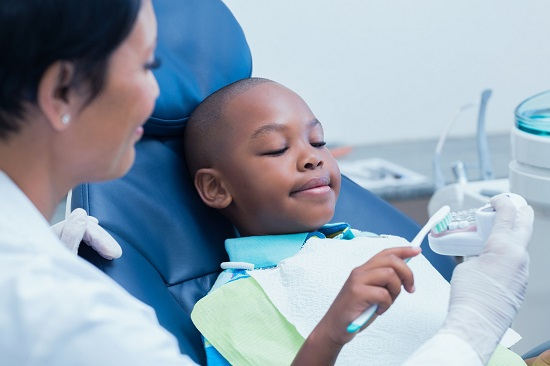 Child in dental chair brushing tooth model.