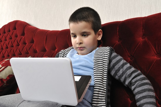 Child sitting on couch looking at laptop on lap.