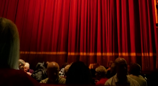move audience looking at red curtain
