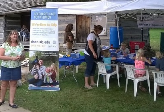 DSCC tent at state fair shows vertical banner with children coloring in the background