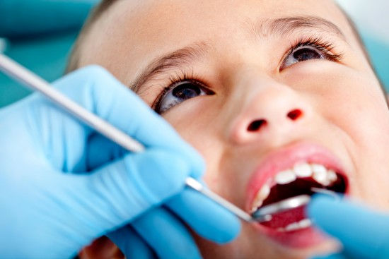 Kid at the dentist getting his teeth checked