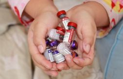 Cupped hands holding multiple vaccine vials