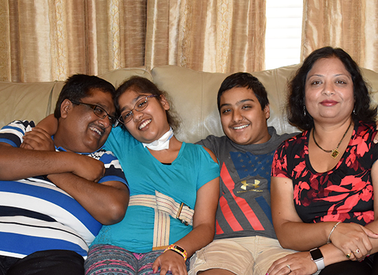Saurabh Agarwal smiling and seated with his daughter, Radhika; son, Ayush; and wife, Mukta.
