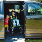 Payton sits in his wheelchair inside a van equipped with a ramp.