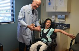 Dr. Keith Gabriel smiles as he holds patient, Bayan's hand