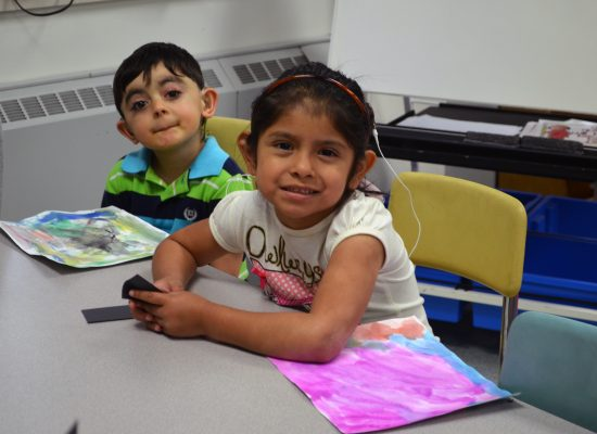 Young girl and both with hearing aids sitting and smiling in a classroom.