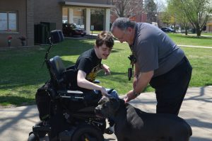 Jacob Flynn pets the dog of Quincy University's Director of Safety and Security Sam Lathrop.