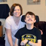 Cheryl and Jacob Flynn smiling together in their Quincy University apartment.