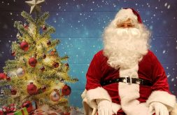 Santa Claus poses in front of a Christmas tree backdrop at the DSCC Mokena Regional Office.