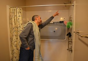 Jaouad Barmaki explains how the shower lift works in his family's new, accessible bathroom.