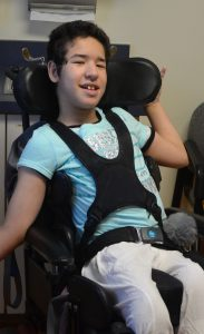 DSCC participant Bayan Barmaki smiles while sitting in her wheelchair during a medical appointment