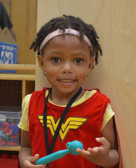 Little girl with hearing aids smiling while wearing a Wonder Woman costume