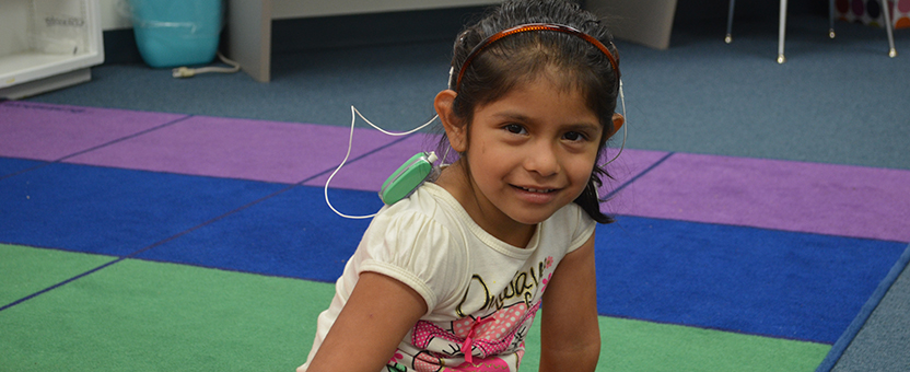 Young girl with hearing aids smiles while sitting on a classroom rug