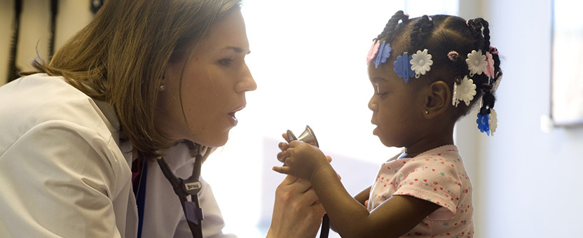 Doctor holds stethoscope in front of young girl