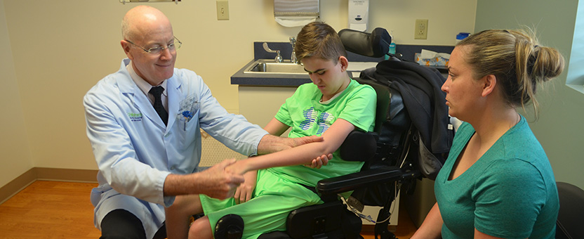 Pediatric orthopedic surgeon checks the arm of a DSCC participant during an orthopedic clinic