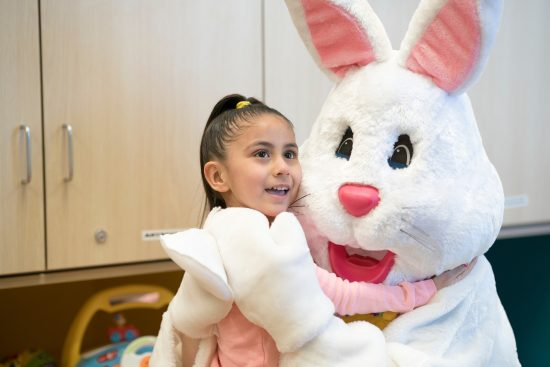 Little girl smiles while hugging the Easter Bunny