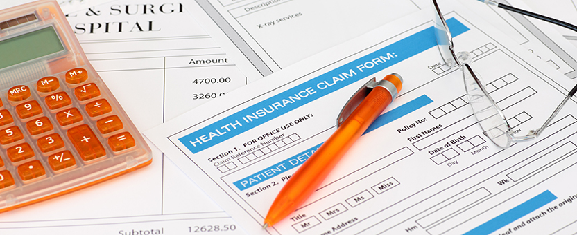 stack of health insurance forms with pen, calculator and pair of reading glasses
