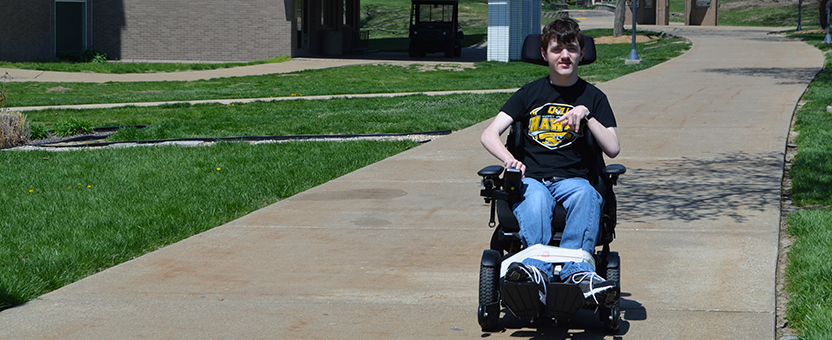 DSCC participant Jacob Flynn traveling in his wheelchair on the Quincy University campus