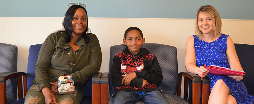 Adolescent boy and his mother smile while sitting in a clinic waiting room with their DSCC Care Coordinator