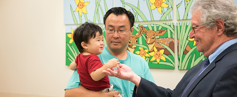 Young boy shakes physician's hand while in his father's arms