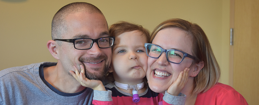 Young girl with tracheostomy tube smiles while posing between her mom and dad and holding their faces
