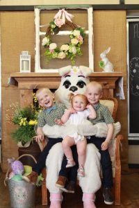 Eloise Hoffman and her two older brothers sitting together on the Easter Bunny's lap