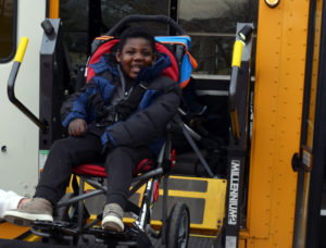 Stanton Whitted smiles as his wheelchair is lowered from his school bus