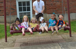 Six young children with hearing loss laugh as they sit on a swing together