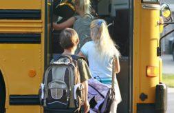 Three students boarding a school bus