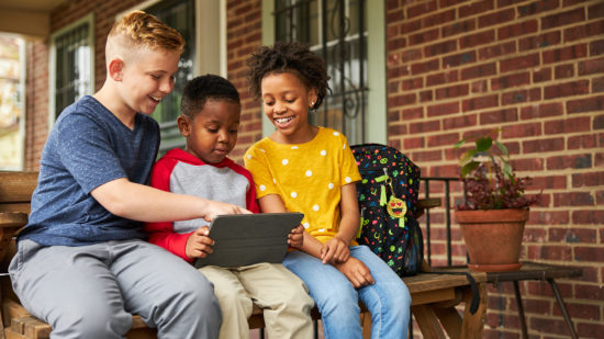 Three kids looking at a laptop together while sitting on a porch