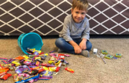 Axel Johnson sits with an overturned bucket of Halloween candy that he cannot eat