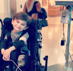 Nash Stieman smiles as he sits in his wheelchair and is hooked up to an IV.
