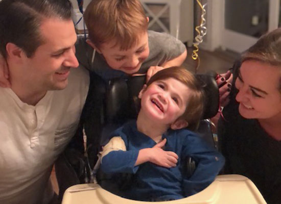 Nash Stineman smiles while surrounded by his mom, dad and older brother.