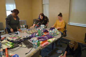 Springfield and Central Administrative Office staff wrap presents for Club Compass students.