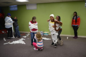 """Club Compass students and DSCC staff laugh as they wrap each other in toilet paper to build a """"snowman"""""""