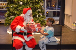 Santa gives a stack of gifts from DSCC staff to an eager Club Compass student.