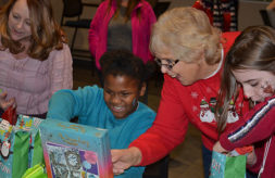 A Club Compass student smiles as she opens a Christmas present donated by Division of Specialized Care for Children Staff
