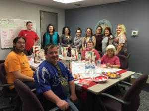 DSCC's Olney staff pose during their thank-you holiday party for the office's cleaning crew.
