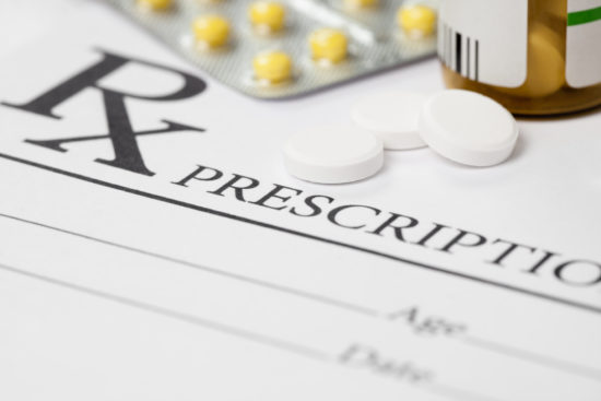 Medical prescription and several pills on table