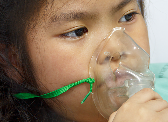Young girl holding an oxygen mask up to her face