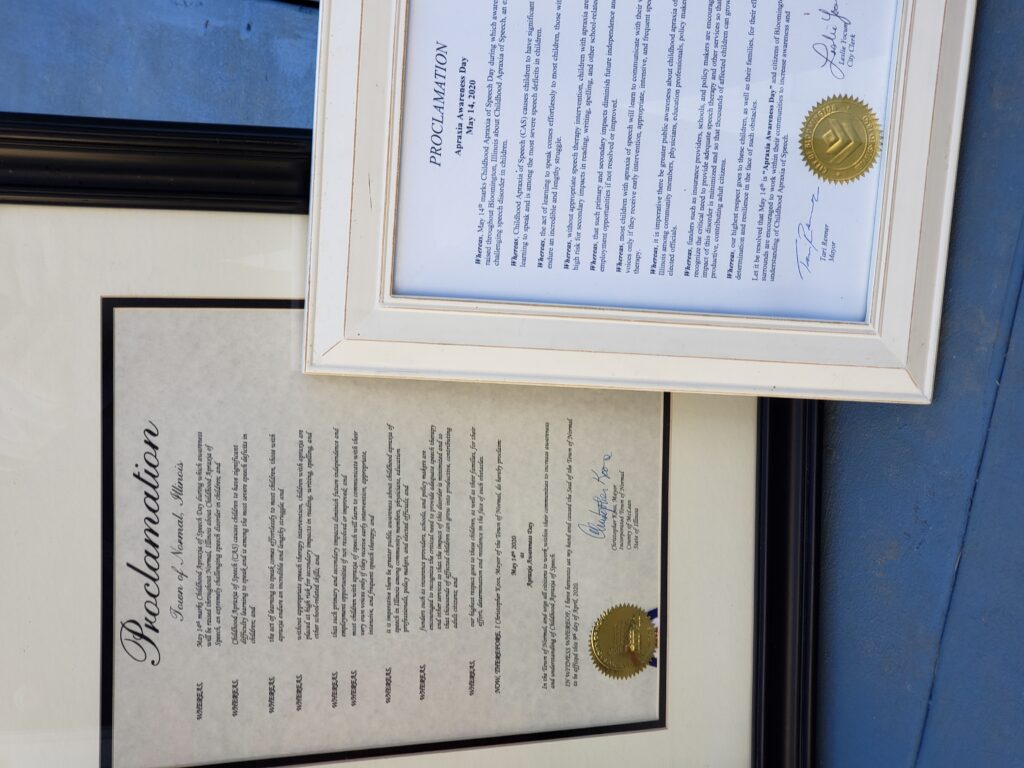 Framed Apraxia Awareness Day Proclamations for the city of Normal and the city of Bloomington.