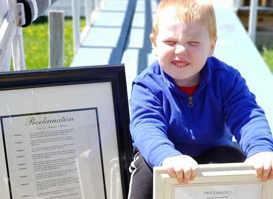 Eldon smiles while holding a framed copy of his city's Apraxia Awareness Day proclamation