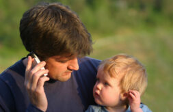 A young son mimics his father who is talking on his mobile