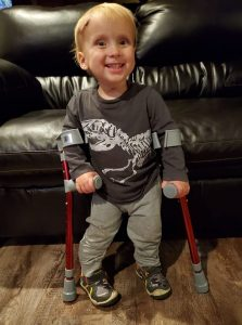 Ryker Miller smiles while standing with his crutches