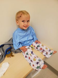 Ryker, wearing a hospital gown and pants, smiles before having an MRI