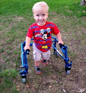 Ryker Miller smiles while walking outside with the assistance of his walker.