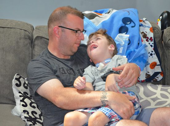 A medically complex little boy smiles up at his father while sitting in his arms