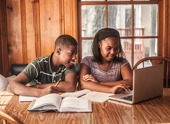 A brother and sister look at a laptop screen together while doing homework