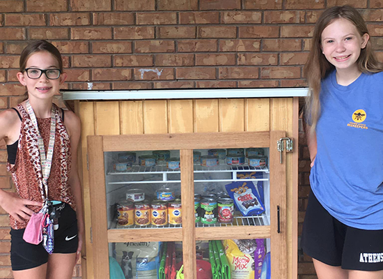 Emma Wiker and her sister, Ellen, stand on either side of a community pet pantry they opened in Athens, Ill.